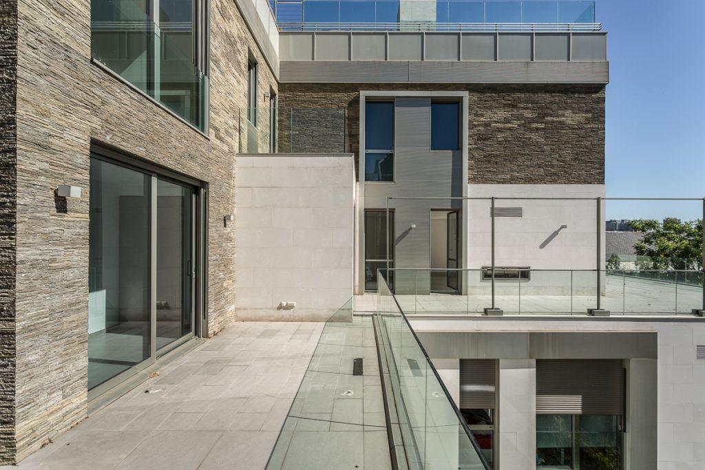 Fotografía desde la terraza de un duplex con grandes ventanas y estilo moderno.