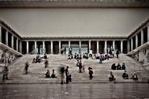 Fotografía del Alta de Pérgamo desde la parte inferior viéndose diversasp personas sentadas en sus escaleras o en movimiento