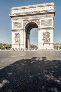 Fotografía del Arco de Triunfo parisino en un día soleado con la glorieta desierta de coches