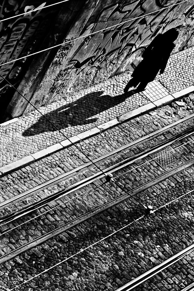 Fot en blanco y negro y desde arriba de la subida a la Gloria, en Lisboa. Se ve una persona en la acera, proyectando su sombra paralela a los railes del tranvía.