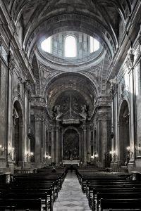 Fotografía del interior de la basílica que ofrece una visión de la nave central y parte de la cúpula por donde se filtran los rayos del sol