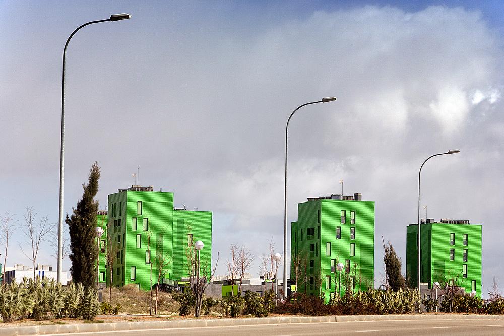 Fotografía de tres edificios residenciales de nueva arquitectura y color verde que contrastan con tres farolas en primer plano