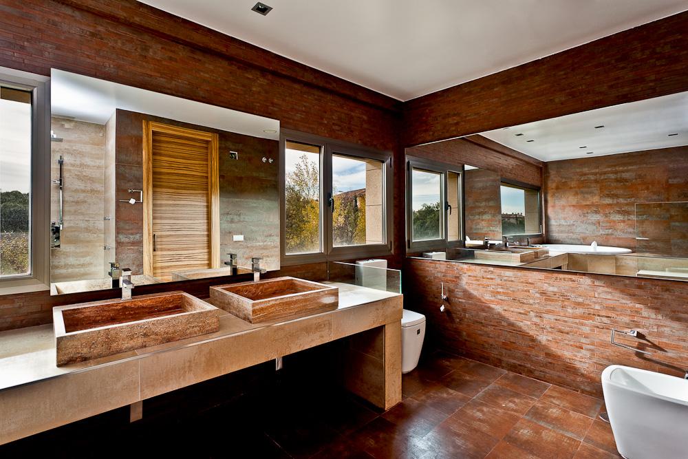 Fotografía de un gran baño con grandes espejos y ventanales y donde se distinguen los distintos sanitarios, un lavabo de dos senos y un gran jacuzzi reflejado