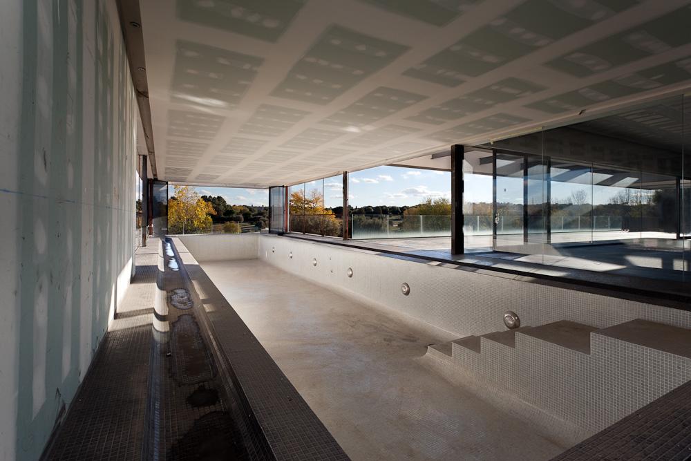 Fotografía de una gran piscina que parece salir de la casa aunque siempre bajo el techo de la misma. Goza de grandes ventanales