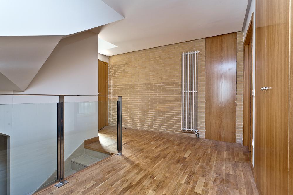 Fotografía de un recibidor en tonos cálidos, con suelo de tarima, una pared de ladrillo visto, puertas de servicios y armarios, escalera descendente con barandilla de cristal y gran radiador de pared.