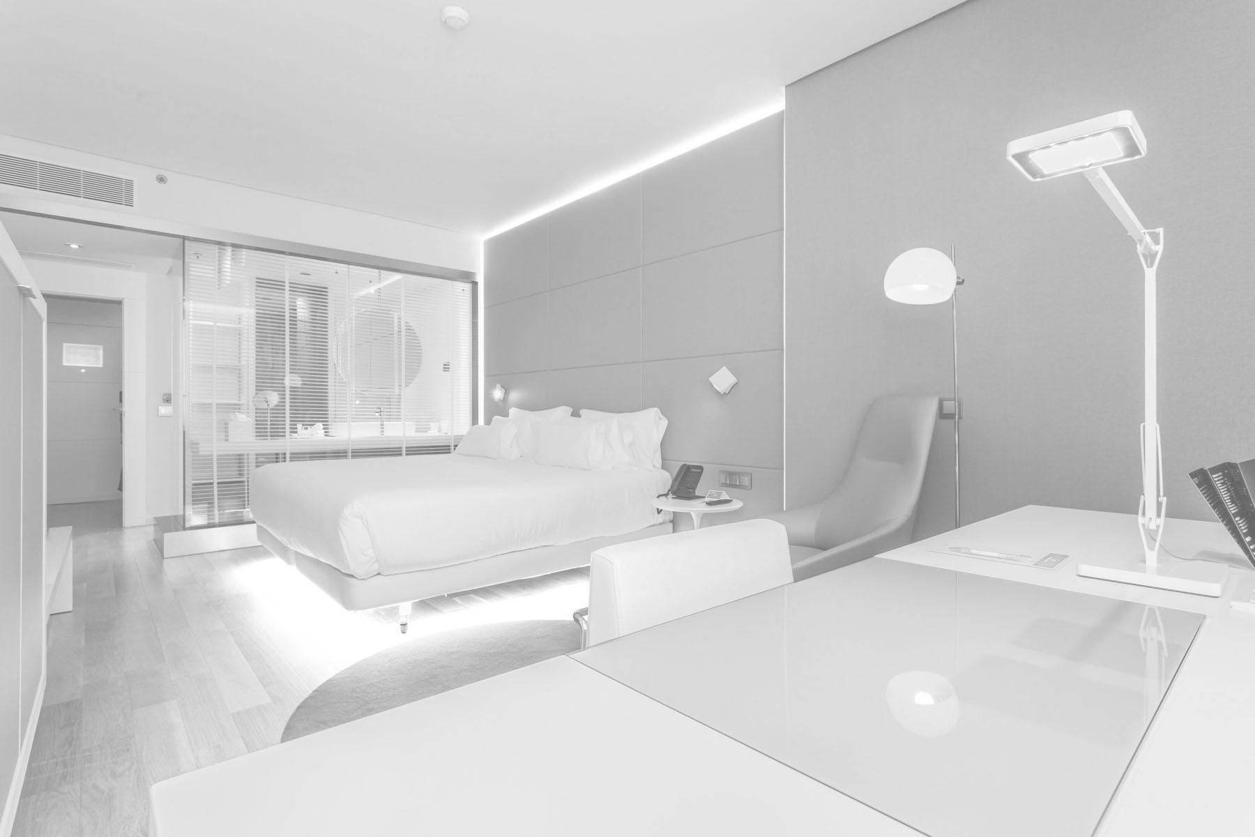 Habitación de hotel de 4 estrellas con el escritorio en primer término, una gran cama y un baño separado por una cristalera semi transparente