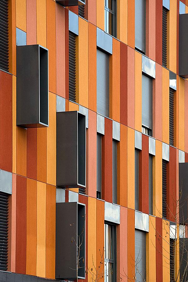 Fotografía de detalle de fachada de edificio de viviendas sociales de nueva arquitectura y tonos naranjas