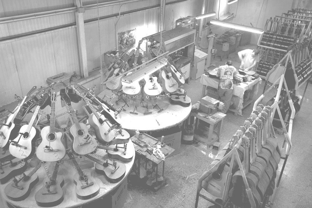Proceso de producción de guitarras españolas, con numerosas guitarras secándose y un par de técnicos trabajando.