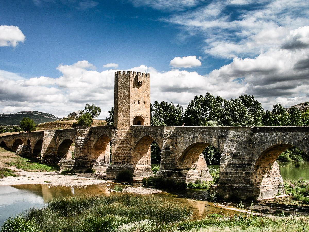 Fotografía del imponente puente de sillares y con una torre fortificada en el medio, sobre un río Ebro que no lleva demasiada agua