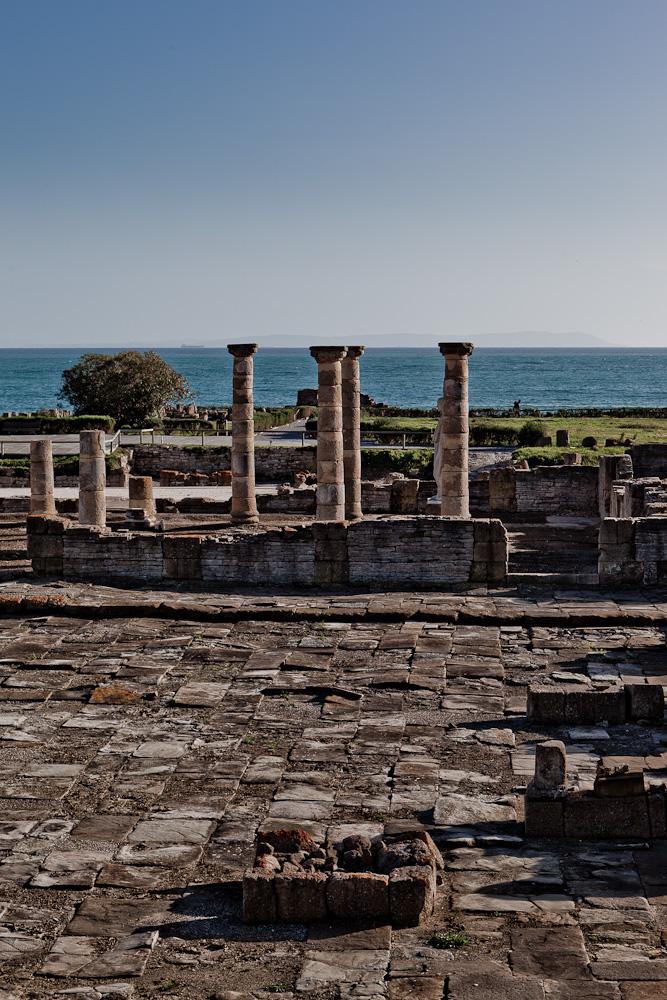 Fotografía con vistas al mar de parte de las ruinas donde sobresalen unas columnas que, al coincidir con la línea de horizonte, parecen sujetar el cielo.