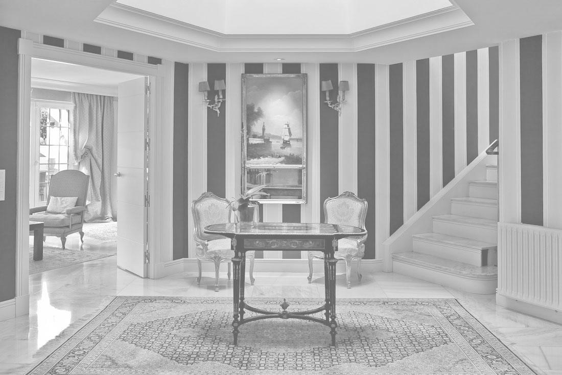 Hall de vivienda de lujo con entrada a salón y escalera a planta superior