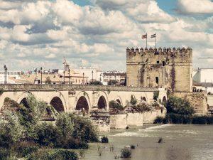 Vista del puente romano desde la parte exterior de la ciudad bajo un cielo claro con nubes altas