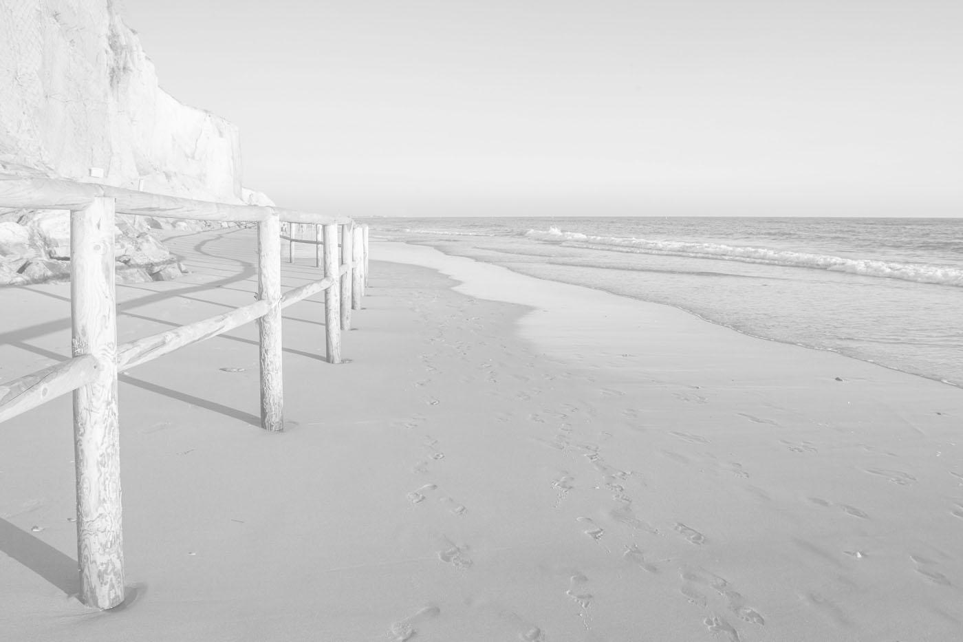 Playa de la Fontanilla, Conil. Vista de una playa infinita con una barrera de madera protegiendo la zona del acantilado.