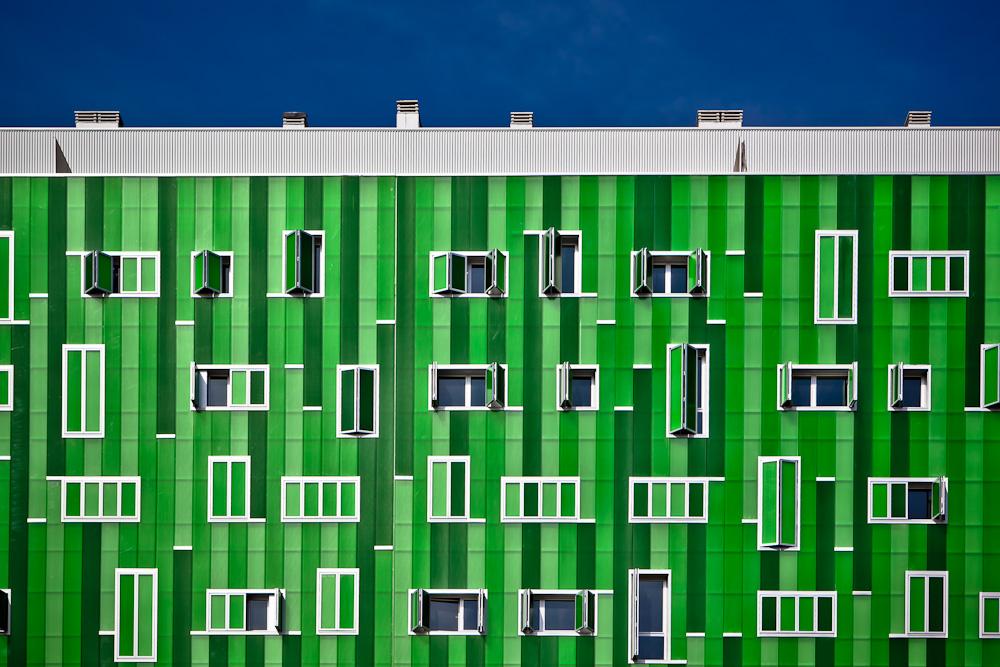 Fotografía de un edificio de viviendas con la fachada compuesta de planchas de plástico en distintas tonalidades de verde