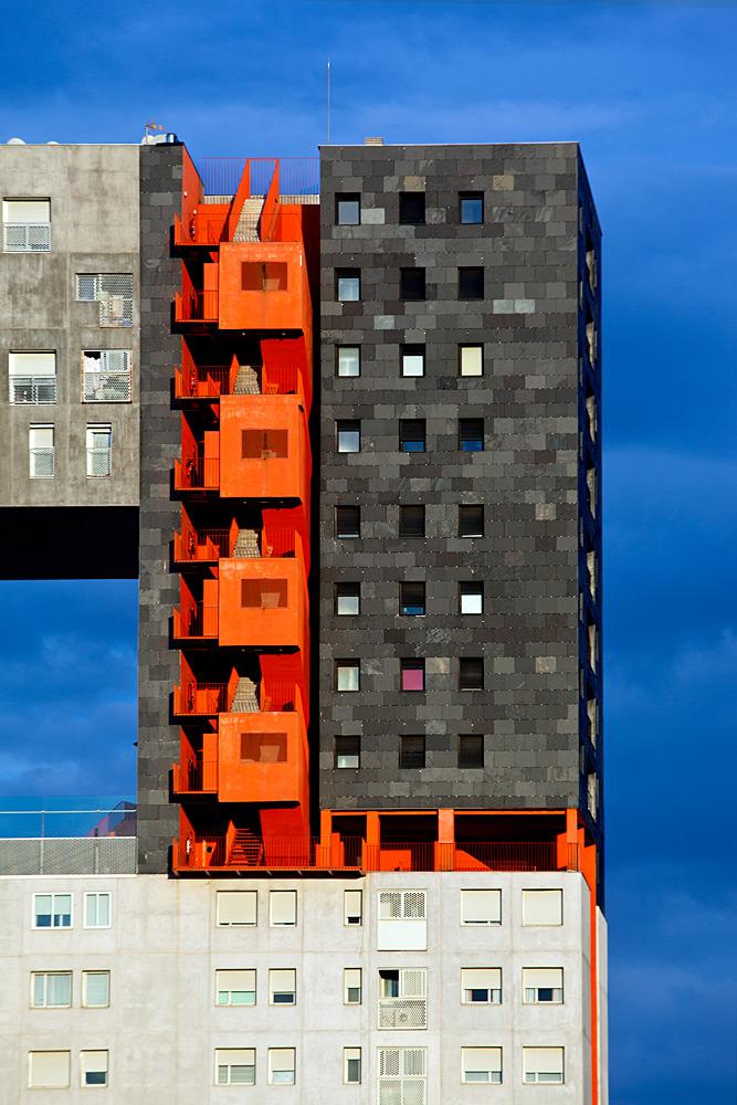Fotografía de la esquina superior derecha de un edificio de viviendas sociales de nueva arquitectura en tonos grises y naranja
