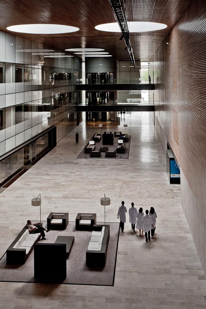 Fotografía del interior de un hospital con un gran atrio cubierto por cuya parte inferior camina un grupo de médicos
