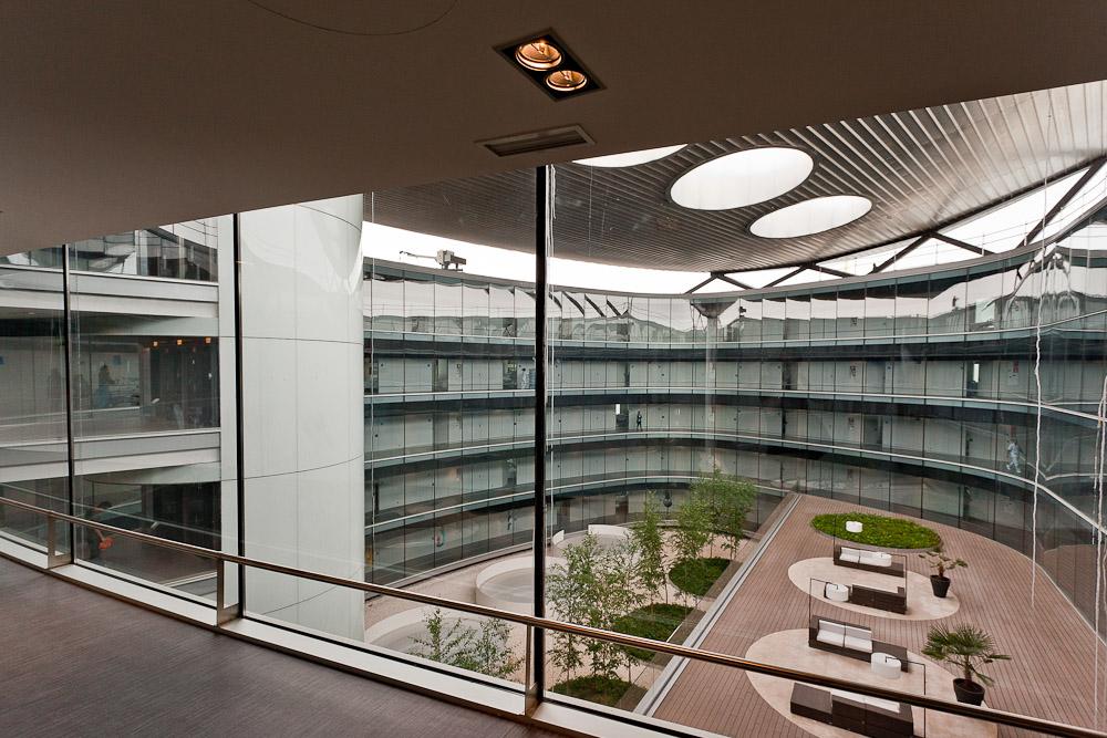 Fotografía de las vistas a un patio cubierto desde uno de los pasillos con paredes de cristal del hospital