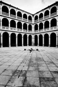 Fotografía en blanco y negro de uno de los ángulos del claustro, con las líneas de las badosas convergiendo hacia la base del ángulo opuesto.