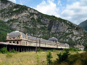 Fotografía con una vista general de la estación y la hierba donde debía haber vías y trenes